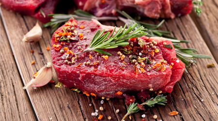 Beef steak with rosemary and spices on a wooden table