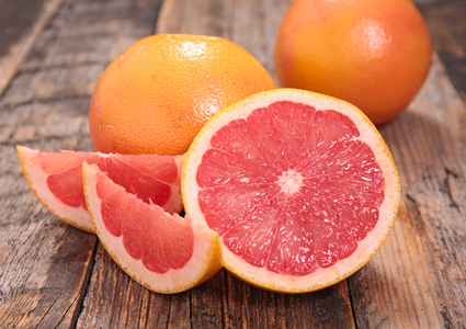 Whole grapefruits, grapefruit wedges and slices on a wooden table