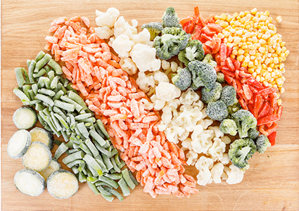 Assorted frozen vegetables on a wooden cutting board