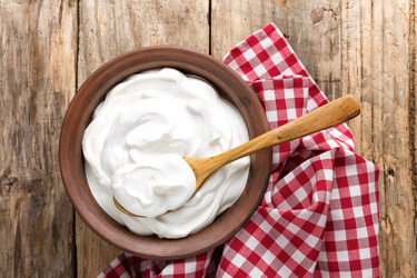 Bowl of yogurt with a wooden spoon