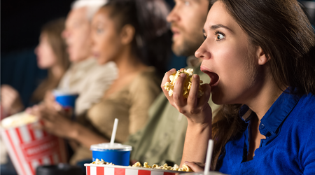 Woman eating while watching a movie
