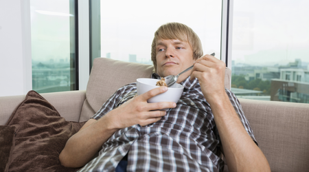Bored man spooning food from a bowl