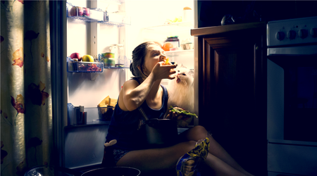 Stressed-out woman and her cat eating at night straight from the fridge