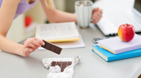 Girl eating chocolate while studying in kitchen