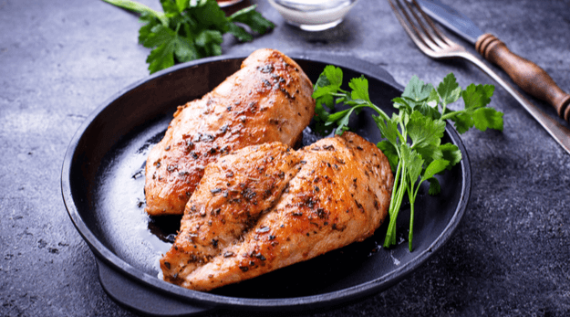 Moist and juicy chicken breast in a black pan