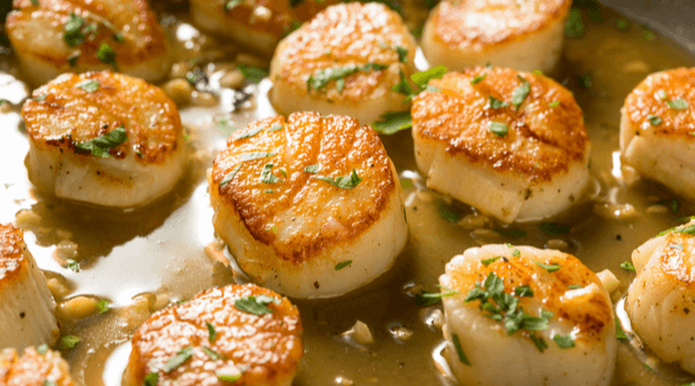 Seared scallops in a sauce with herbs