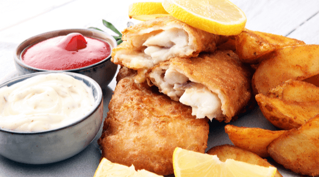 Crispy baked haddock with sauce and lemon slices