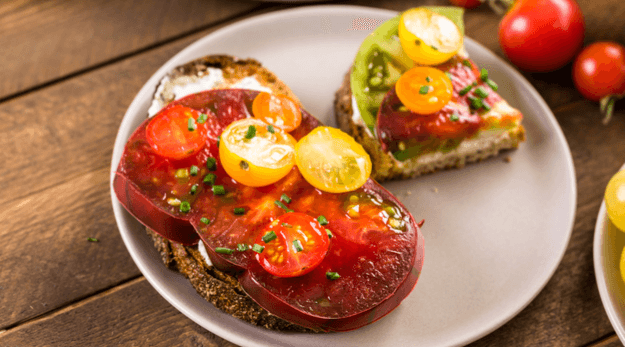 Sprinkle tomato toast with fresh herbs, sea salt, and pepper