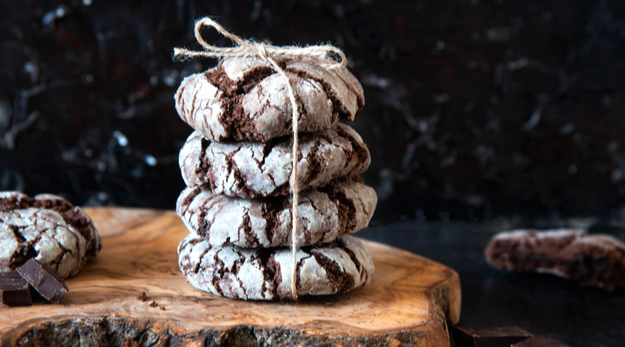 Chocolate crinkle cookies with powdered sugar on a black background