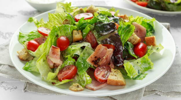 BLT salad with seasoned croutons on a white table
