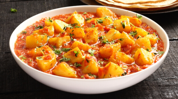 Spicy potatoes with herbs and tomatoes in a bowl